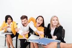 Emotional colleagues sitting in office tries to get folder. Royalty Free Stock Photos