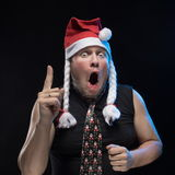 Emotional Comic actor man in cap with braids gesticulates, in anticipation of Christmas and New Year Stock Photo