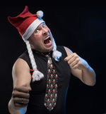Emotional Comic actor man in cap with braids gesticulates, in anticipation of Christmas and New Year Stock Image