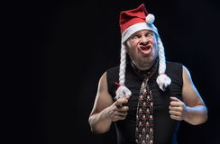 Emotional Comic actor man in cap with braids gesticulates, in anticipation of Christmas and New Year Stock Images