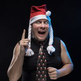 Emotional Comic actor man in cap with braids gesticulates, in anticipation of Christmas and New Year Royalty Free Stock Images