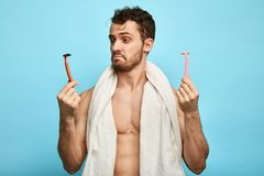 Emotional confused muscular man holding two shavers stock images