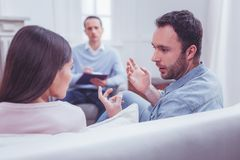 Emotional couple discussing relationships during psychological therapy. Recovering feelings. Close up of emotional motivated couple having active discussion royalty free stock photo
