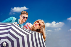 Emotional couple hiding behind the umbrella and having fun on th Stock Image