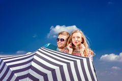 Emotional couple hiding behind the umbrella and having fun on th. E blue sky background Royalty Free Stock Image