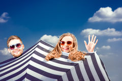 Emotional couple hiding behind the umbrella and having fun on th Royalty Free Stock Photos
