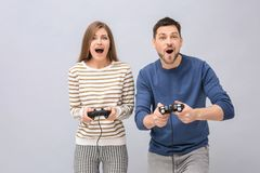 Emotional couple with video game controllers. On grey background Royalty Free Stock Photography