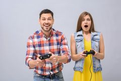 Emotional couple with video game controllers. On grey background Stock Photo