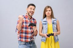 Emotional couple with video game controllers. On grey background Royalty Free Stock Images