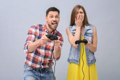 Emotional couple with video game controllers. On grey background Stock Images