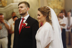 Emotional couple during wedding ceremony, handsome happy groom a. Nd beautiful bride tearing up during priests speech at wedding ceremony in christian church Stock Photography