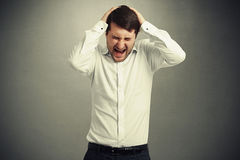 Emotional creaming man in white shirt Royalty Free Stock Images