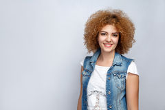 Emotional curly hair girl in casual style. Portrait of beautiful happy curly mixed race girl in casual style is smiling. looking at camera. studio shot on light Stock Photo