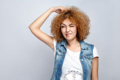 Emotional curly hair girl in casual style. Portrait of beautiful thoughtful curly mixed race girl in casual style is thinking. studio shot on light gray Royalty Free Stock Image