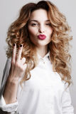 Emotional curly woman gesturing peace sign by fingers and making duck face. Girl with marsala lips in  white shirt posing at camer Stock Photos
