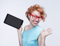 Emotional cute red-haired girl holding tablet computer, opening hands. Royalty Free Stock Images