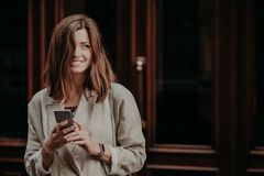 Emotional delighted happy brunette young woman with dark hair, uses mobile phone for texting messages, dressed in elegant raincoat stock photos