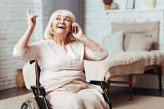 Emotional disabled aged woman talking on cell phone Royalty Free Stock Image