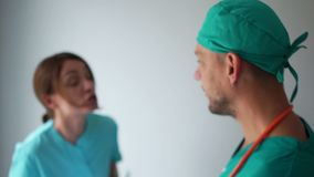 Emotional dispute between two doctors. A male doctor and a female assistant discuss the diagnosis and treatment. Medical
