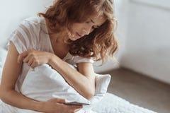 Emotional erschöpfte Frau, die zu Hause Smartphone verwendet Lizenzfreies Stockfoto