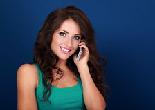 Emotional excited young woman talking on mobile phone on blue ba Stock Photo