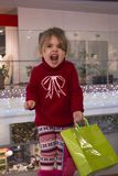 Emotional and expressive little girl in a red sweater in the shopping mall. Portrait of a pretty little girl in a red sweater with gifts at the beautifully Royalty Free Stock Photos