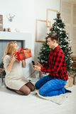 Emotional family portrait. The cheerful pregnant woman is receiving the Christmas gift from her handsome husband. They royalty free stock photos