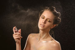 Emotional fashion portrait of beautiful women with bright makeup. Holding perfume bottle. Spraying of water in motion. Wet skin. Stock Images