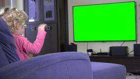 Emotional female child looking at green screen chroma key tv stock video