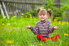 Emotional five-year girl sitting in grass. Royalty Free Stock Photography