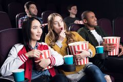 Emotional friends with popcorn and soda watching movie. In cinema royalty free stock photography