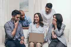 Emotional friends using laptop while sitting on sofa at home Stock Photo