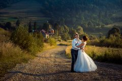 Emotional full-length shot of the cheerful newlywed couple laughing and having fun during the walk along the countryside royalty free stock images