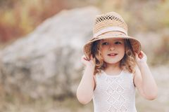 Happy little girl wearing a hat outdoors. Emotional funny little girl outdoors Stock Photo