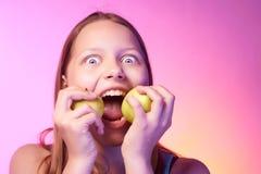 Emotional funny teen girl eating apple Royalty Free Stock Photos