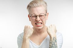 Outraged man gestures angrily, being irritated, outraged. Emotional furious artist man clenching white perfect teeth, squeezing fists, being irritated with loud Royalty Free Stock Image