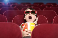 Emotional girl at the 3D cinema. Shoked young woman with popcorn in 3D movie Stock Photos