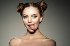 Emotional girl. Beautiful modern model shows tongue Positive wom Stock Images