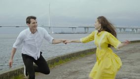 Emotional girl and boy dance jive on a pier with yachts in the background. A cheerful fair haired young woman in yellow dress and her joyful young man in black stock video footage