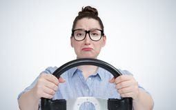 Emotional girl in glasses with car steering wheel, auto concept Royalty Free Stock Images