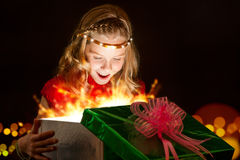 Emotional girl opening Christmas present. Stock Image