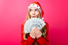 Emotional girl in a red sweater and Santa Claus hat, in admiration holding money on a red background. stock photos