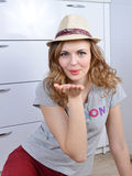 Emotional girl sits on a floor and poses in a hat stock photography