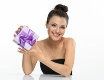 Emotional Girl with violet present and bow. The beautiful girl smiling holds a gift in a box on a white background Royalty Free Stock Photography