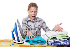 Emotional girl with washed linen around ironing board and iron i Royalty Free Stock Images