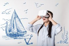 Emotional girl wearing virtual reality device and feeling impressed Stock Image