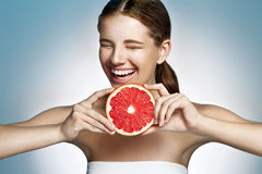 Emotional glossy girl with grapefruit Stock Image