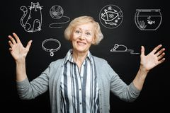 Emotional granny smiling while thinking about her adorable pets. Pets lover. Cheerful kind senior lady smiling and putting her hands up while being alone and Stock Image