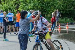 LVIV, UKRAINE - MAY 2018: Emotional greeting at the finish of a cyclist`s athlete and rewarding him with a medal. Emotional greeting at the finish of a cyclist`s royalty free stock image