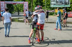 LVIV, UKRAINE - MAY 2018: Emotional greeting at the finish of a cyclist`s athlete and rewarding him with a medal. Emotional greeting at the finish of a cyclist`s royalty free stock photography